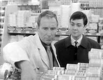 Detective Constable Broome (Leslie Lawton) visits Frank (Alfred Burke), who is working in a supermarket, stacking shelves.