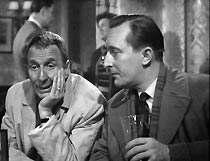 Frank (Alfred Burke) enjoys a drink with fellow lodger Mr Enright (Peter Cellier)