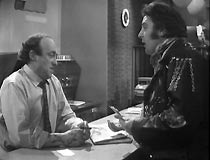Harry (Terence Rigby) operates his scam on the cafe owner (Ken Jones)