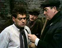 Tom (John Nightingale) is threatened with a cutthroat razor by thugs Dodger Green (Peter Bartle) and Dickie Edgar (Peter Thornton).