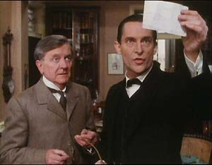 Hilton Cubitt (Tenniel Evans) and Holmes (Jeremy Brett) examine Cubitt's transcription of the dancing men pictograms.